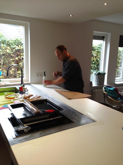 Het werkblad van de keuken wordt afgekit door monteur Jan.